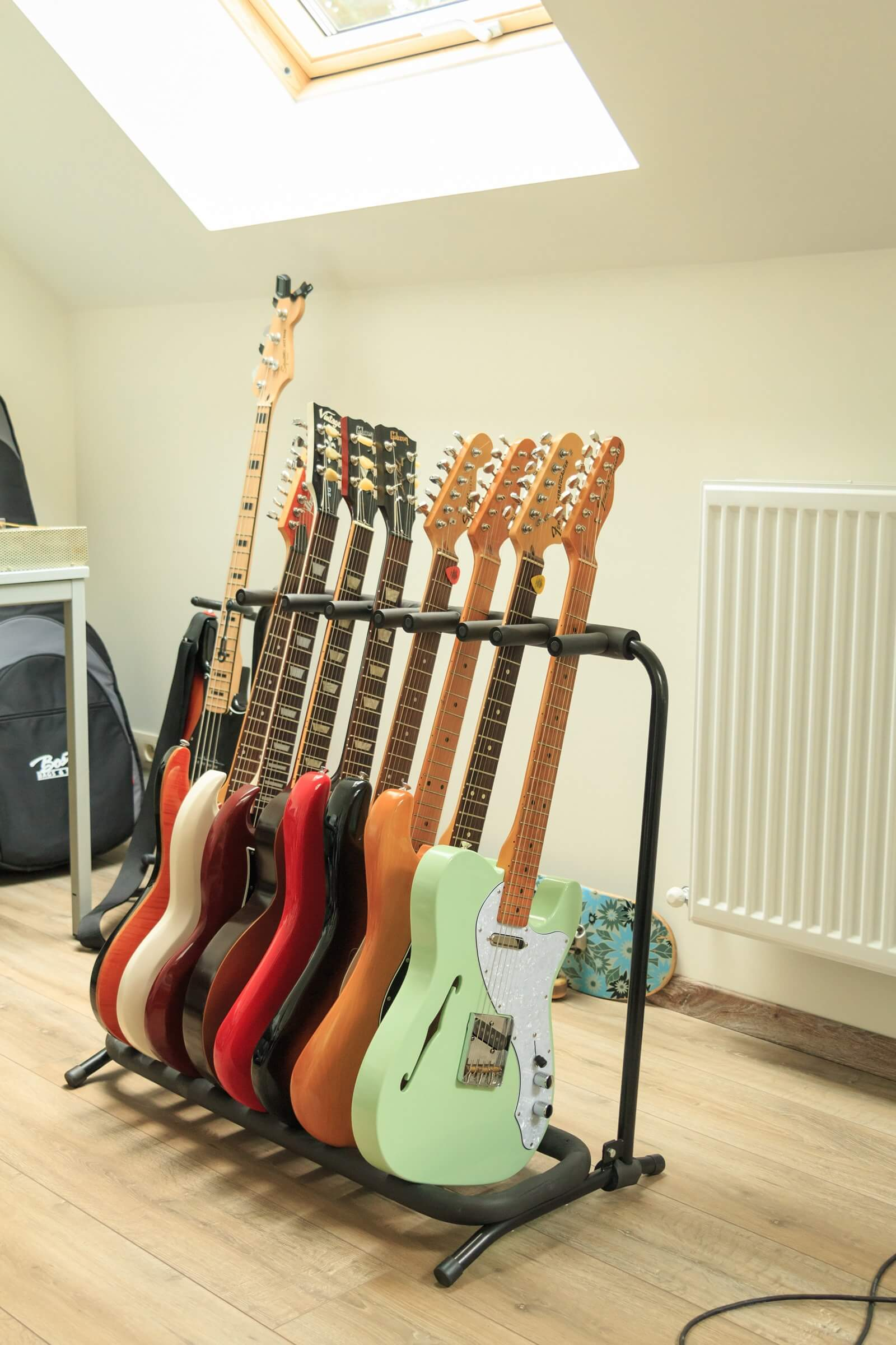 A Telecaster Thinline on a guitar rack holding several electric guitars